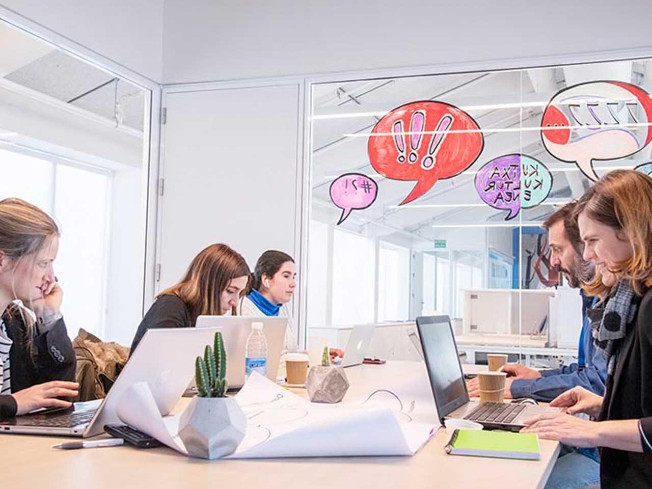 Equipo de cinco personas trabajando en una sala.