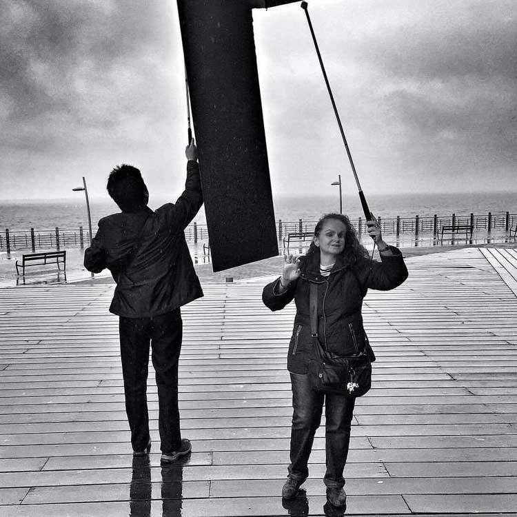Dos personas con discapacidad visual y usuarias de bastón palpando una escultura.