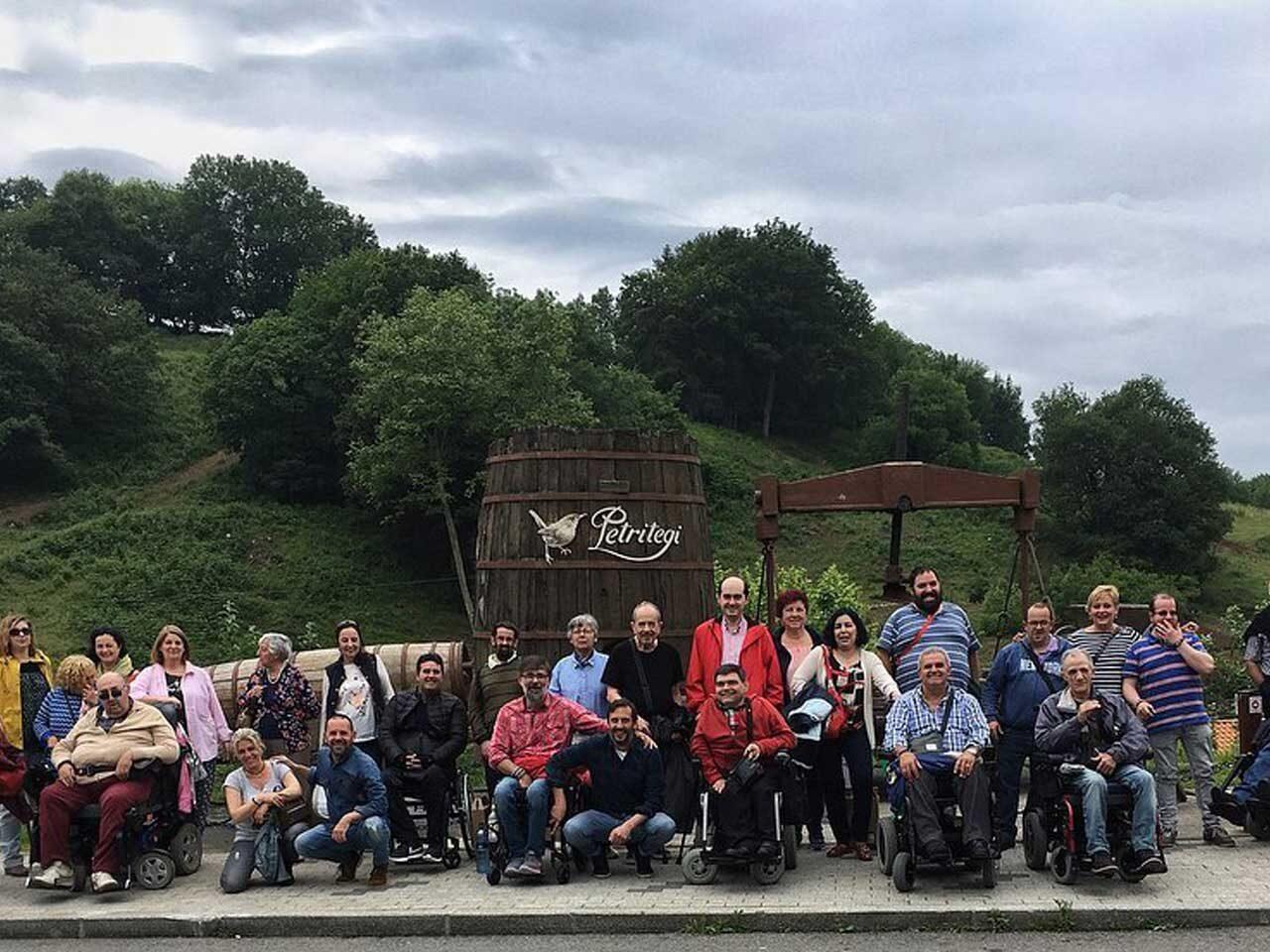Grupo de personas en la sidrería Petritegi, algunas de ellas usuarias de silla de ruedas.