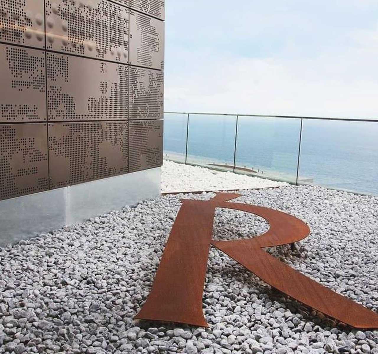 Escultura de la terraza del hotel Akelarre. Una R mayúscula de cobre tumbada sobre pavimento empedrado.